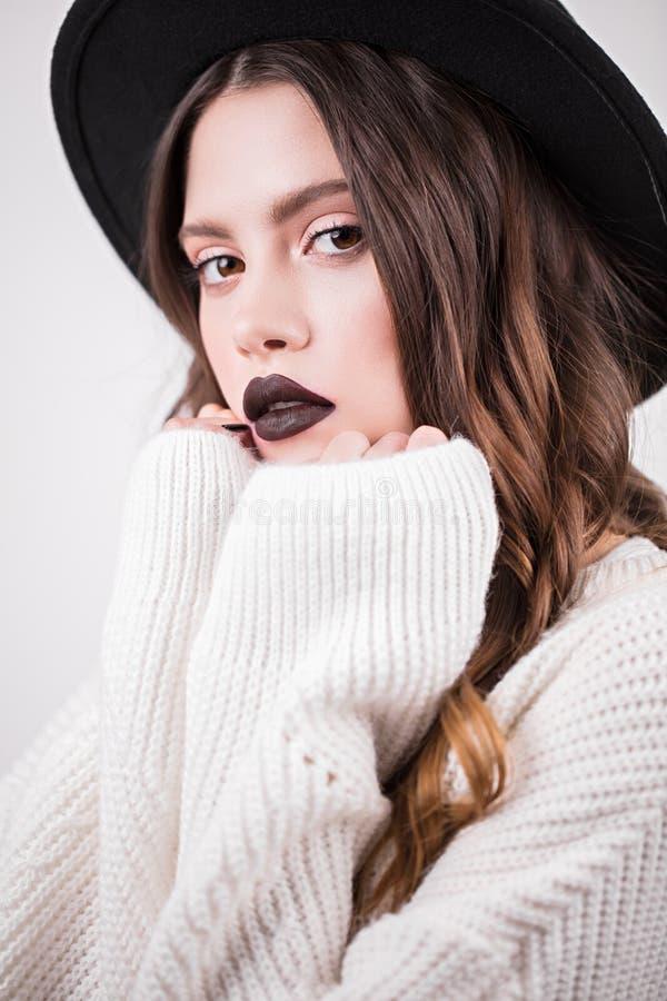 Ciérrese encima del retrato de una mujer atractiva de moda con los labios oscuros en un sombrero y un suéter blanco Una muchacha  foto de archivo libre de regalías