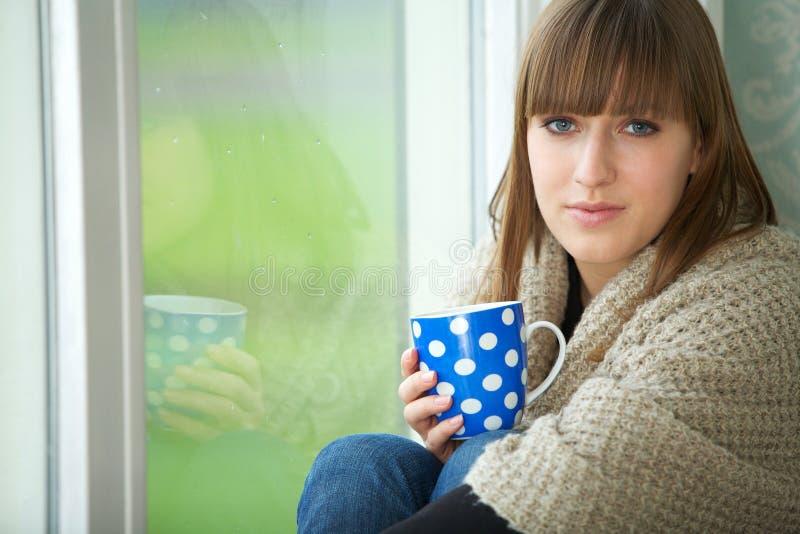 Mujer joven que se relaja por la ventana con la taza de té fotografía de archivo libre de regalías
