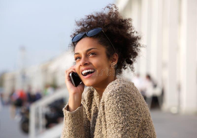 Ciérrese encima del retrato de una mujer joven que sonríe con el teléfono móvil imágenes de archivo libres de regalías