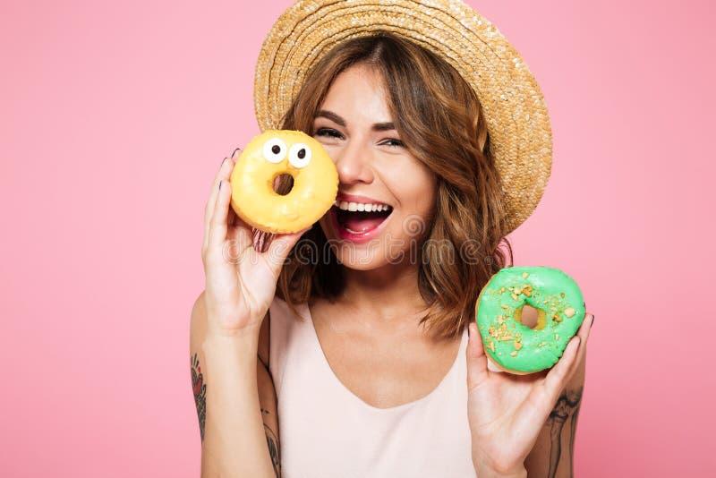Ciérrese encima del retrato de una mujer sonriente divertida en sombrero del verano imagenes de archivo