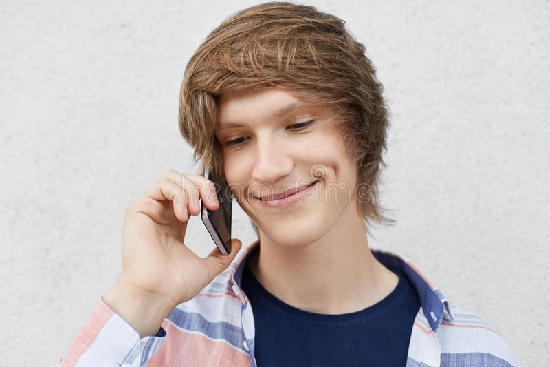 Ciérrese encima del retrato del adolescente hermoso con el peinado de moda, sonriendo suavemente teniendo hoyuelos en las mejilla fotografía de archivo