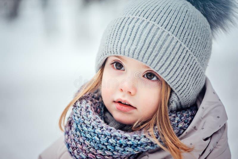 Ciérrese encima del retrato del invierno de la niña pequeña adorable en bosque nevoso imagenes de archivo