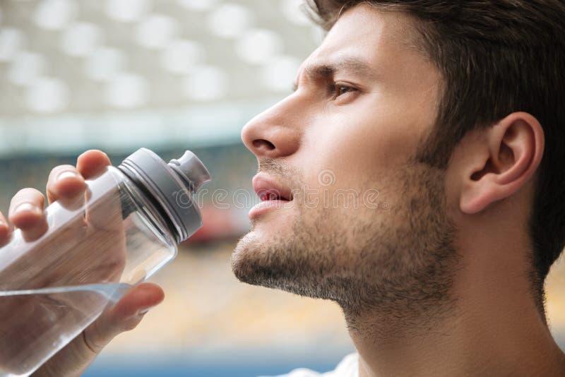 Ciérrese encima del retrato del perfil de un agua potable del hombre hermoso foto de archivo libre de regalías