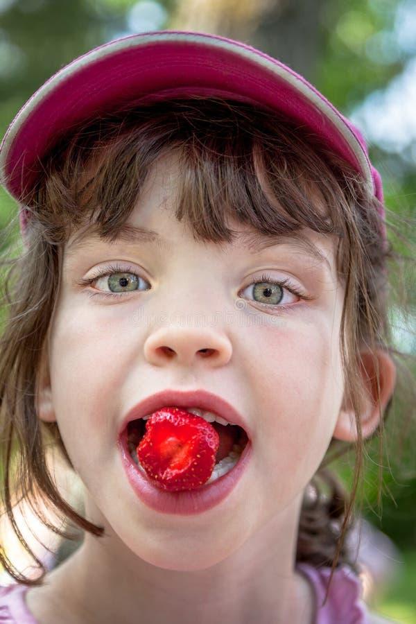 Ciérrese encima del retrato del verano de la chica joven linda en casquillo rosado que come una fresa fotos de archivo libres de regalías