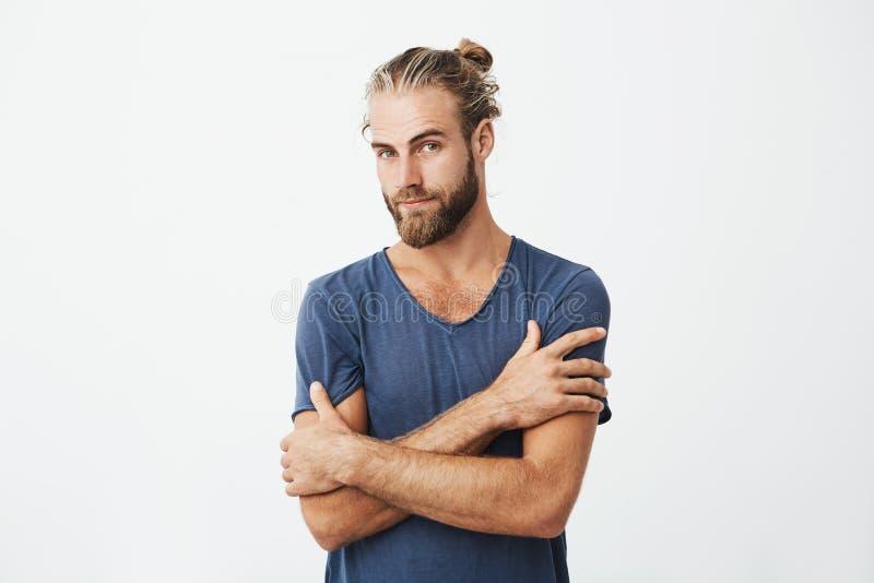 Ciérrese encima del retrato del hombre barbudo atractivo con las manos apuestas de la travesía del peinado en pecho, mirando la c foto de archivo