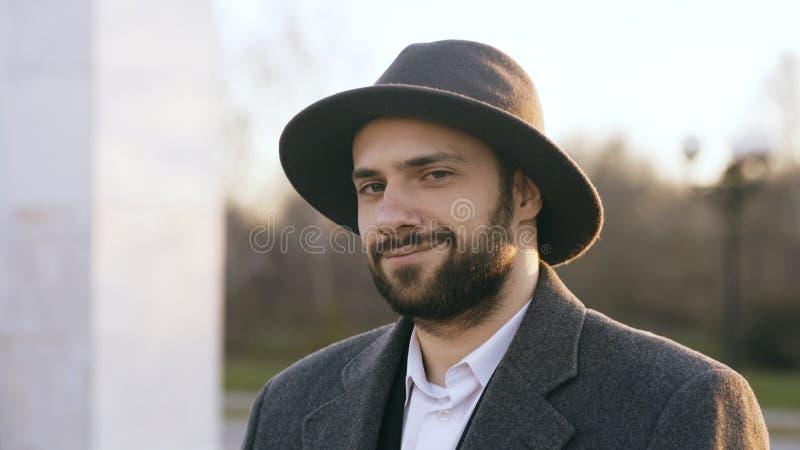 Ciérrese encima del retrato del hombre de negocios joven barbudo del inconformista que sonríe y que mira en cámara en calle al ai imagen de archivo libre de regalías