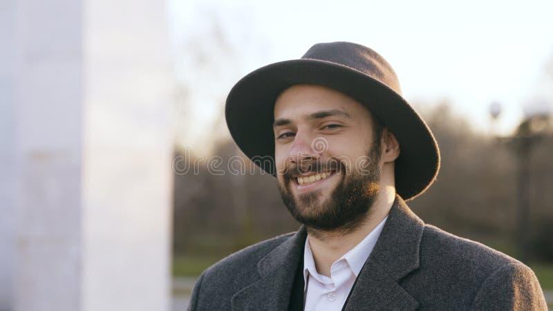 Ciérrese encima del retrato del hombre de negocios joven barbudo del inconformista que sonríe y que mira en cámara en calle al ai foto de archivo libre de regalías