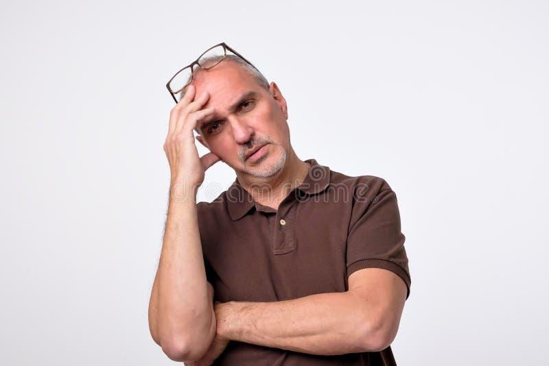 Ciérrese encima del retrato del hombre maduro pensativo en camiseta marrón imagen de archivo libre de regalías