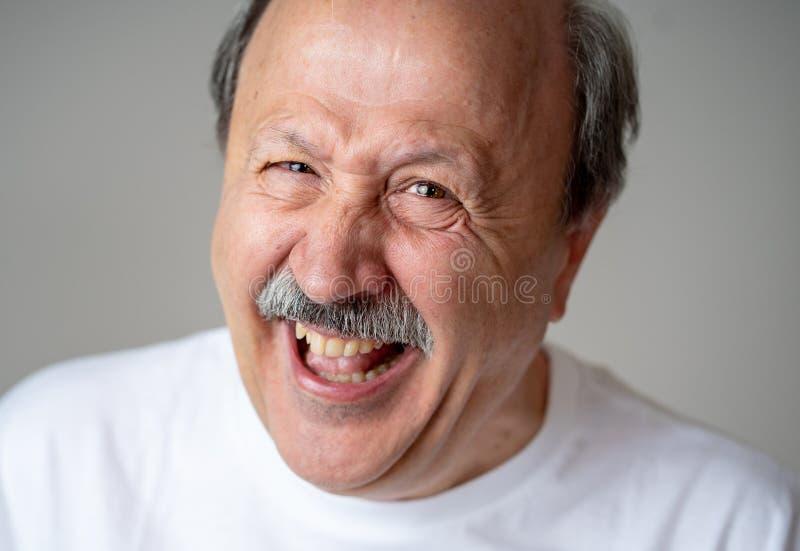Ciérrese encima del retrato del hombre mayor sonriente con la cara feliz que mira la cámara foto de archivo libre de regalías