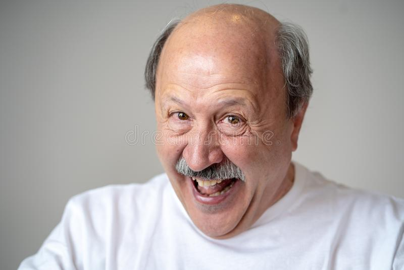 Ciérrese encima del retrato del hombre mayor sonriente con la cara feliz que mira la cámara imagen de archivo libre de regalías