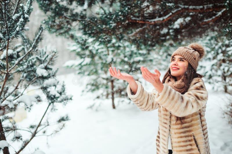 ciérrese encima del retrato del invierno de la mujer joven sonriente que camina en bosque nevoso imagen de archivo