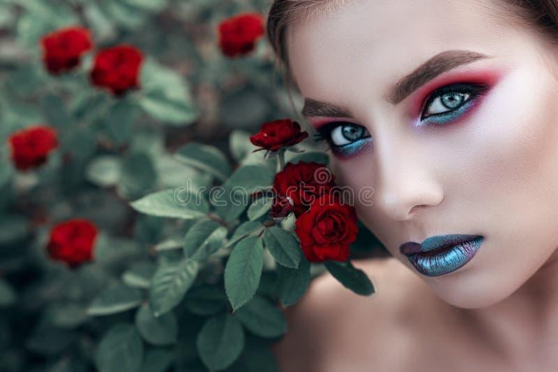 Ciérrese encima del retrato del modelo hermoso joven con artístico componen sentarse en el arbusto color de rosa rojo y la mirada imágenes de archivo libres de regalías