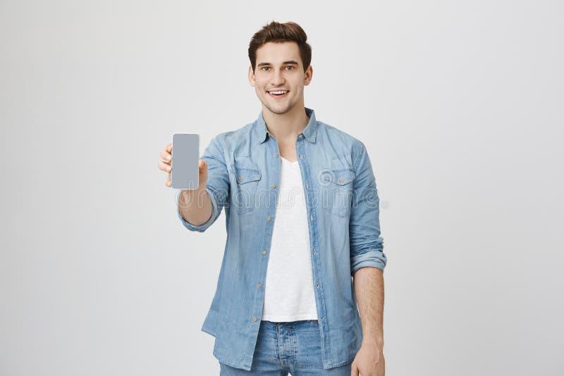 Ciérrese encima del retrato del modelo joven atractivo con el peinado y el equipo de moda, presentando el nuevo smartphone para h imágenes de archivo libres de regalías