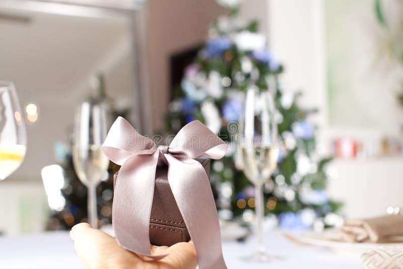 Ciérrese encima del tiro de la mano femenina que sostiene un pequeño regalo envuelto con r fotografía de archivo libre de regalías