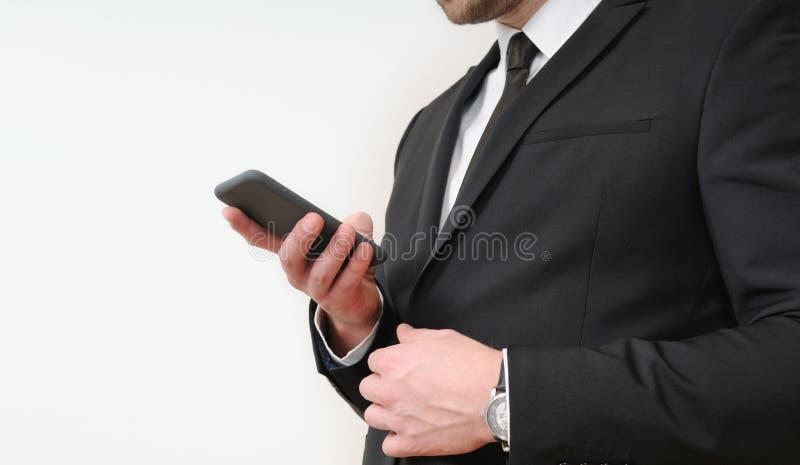 Ciérrese encima del tiro de las manos del hombre de negocios que sostienen un teléfono en el CCB blanco imagenes de archivo