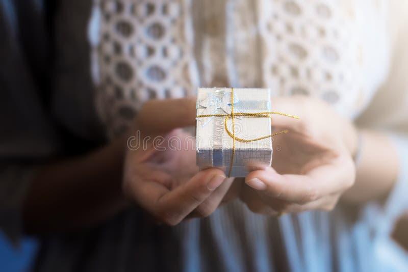 Ciérrese encima del tiro de las manos femeninas que sostienen un pequeño regalo imagenes de archivo