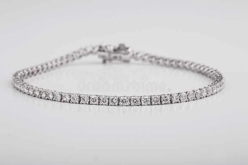 Ciérrese encima del tiro de las pulseras hermosas del diamante en el fondo blanco imagen de archivo