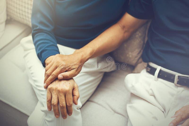 Ciérrese encima del tiro de los pares mayores mayores que llevan a cabo las manos y que las apoyan con uno a imagen de archivo