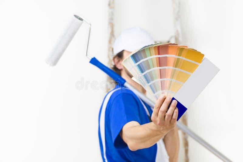 Ciérrese encima del tiro del hombre del pintor que muestra una paleta de colores fotografía de archivo libre de regalías