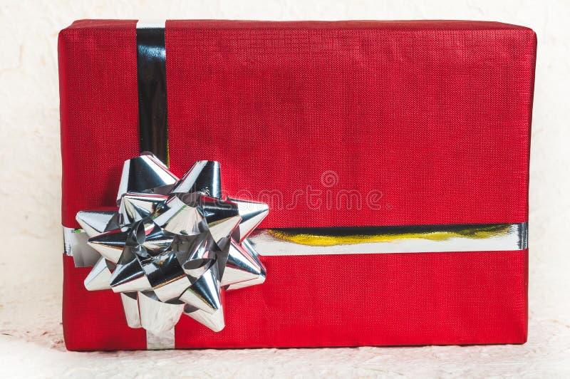 Ciérrese hasta la caja de regalo roja con la cinta y la decoración para el diseño de la Navidad foto de archivo libre de regalías