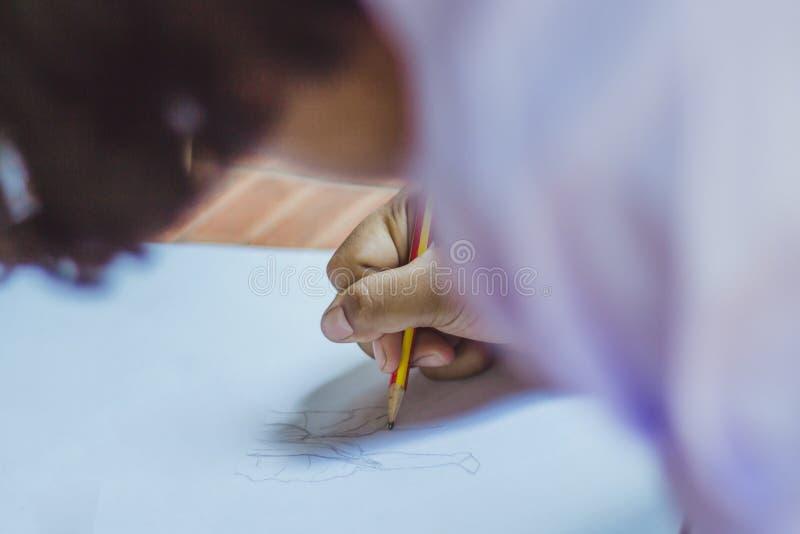 Ciérrese hasta las manos del dibujo de la práctica del estudiante imagen de archivo