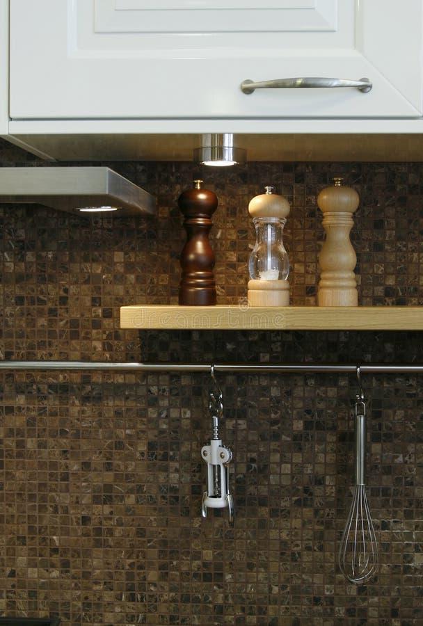 Ciérrese hasta una pared de la cocina con los utensilios en ella fotografía de archivo