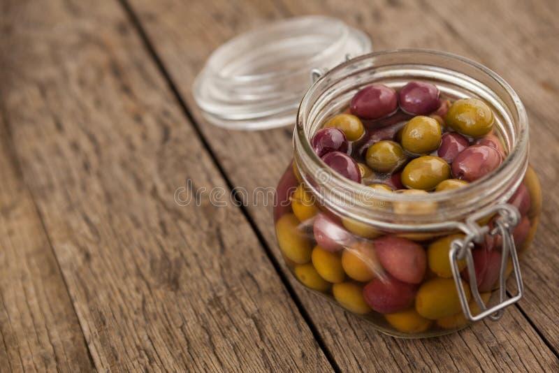Ciérrese para arriba de aceitunas con aceite en el tarro de cristal fotos de archivo libres de regalías