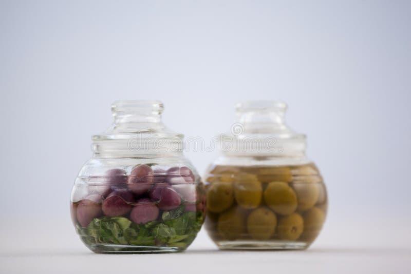 Ciérrese para arriba de aceitunas rojas y verdes en el tarro de cristal fotografía de archivo libre de regalías