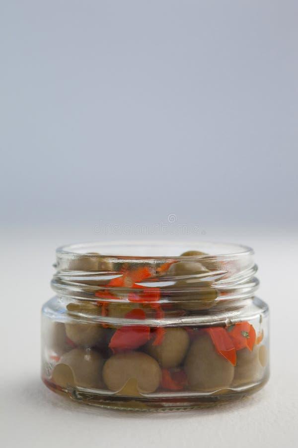 Ciérrese para arriba de aceitunas verdes y de hierbas en el tarro de cristal imagen de archivo libre de regalías