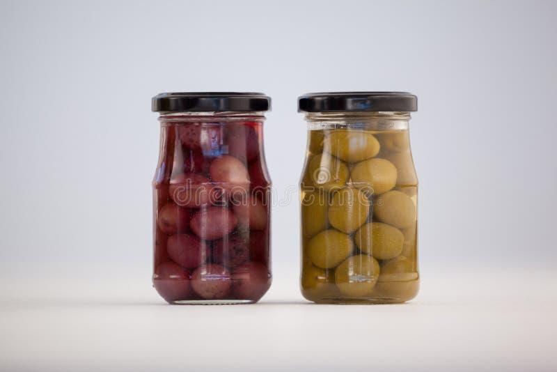 Ciérrese para arriba de aceitunas verdes y marrones en el tarro de cristal fotografía de archivo