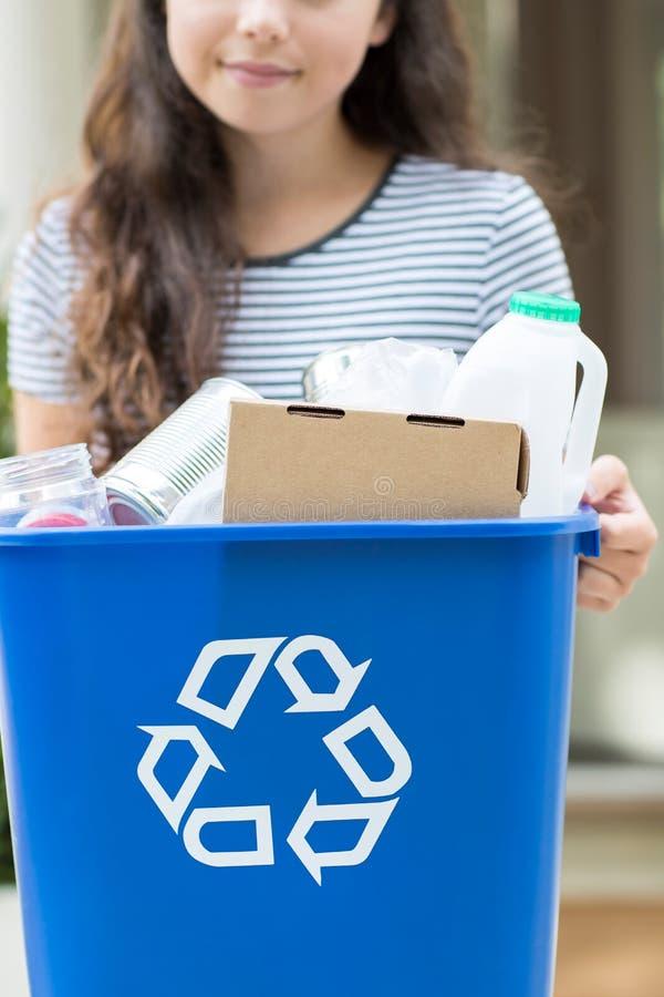 Ciérrese para arriba de adolescente fuera de la papelera de reciclaje que lleva de la casa foto de archivo