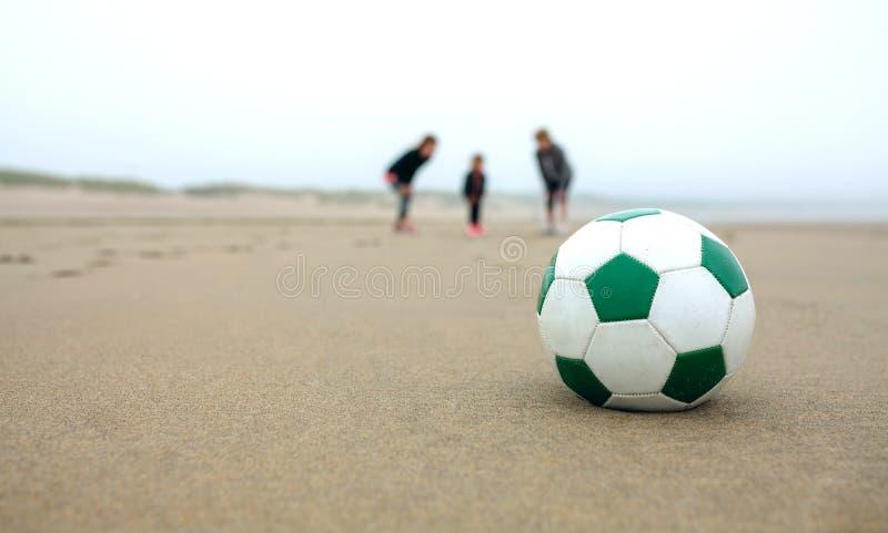 Ciérrese para arriba de balón de fútbol con tres personas fotos de archivo