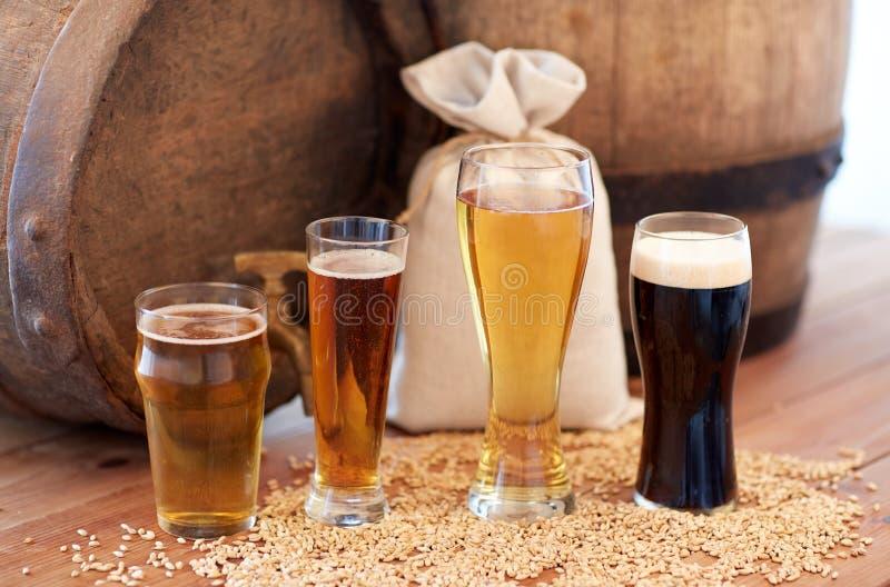 Ciérrese para arriba de barril, de los vidrios y de bolso de cerveza con malta fotos de archivo libres de regalías