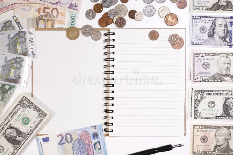 Ciérrese para arriba de billete de banco y de moneda con el cuaderno foto de archivo libre de regalías