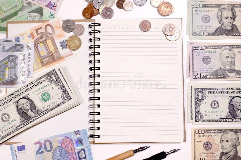 Ciérrese para arriba de billete de banco y de moneda con el cuaderno fotos de archivo libres de regalías