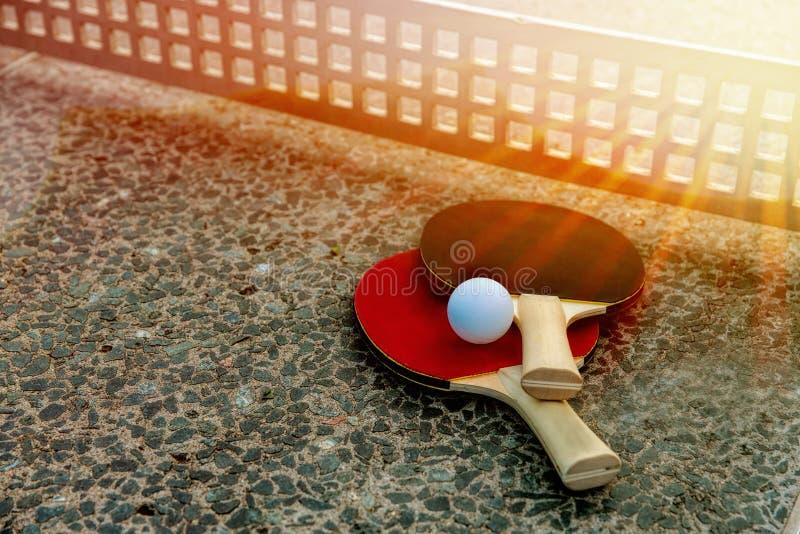 Ciérrese para arriba de bola de ping-pong con las estafas de tenis en la tabla de piedra en luces soleadas, equipo del tenis para fotografía de archivo