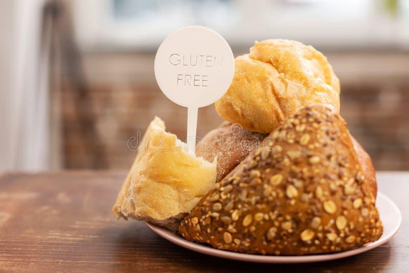 Ciérrese para arriba de bollos y de pan sin el gluten que se coloca en la tabla imagen de archivo