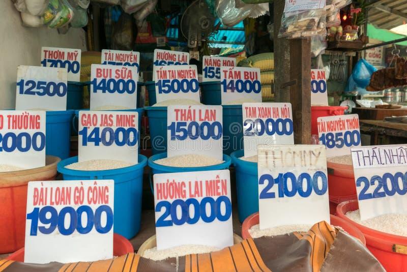 Ciérrese para arriba de bolsos del arroz en un mercado local en Vietnam con precio imagen de archivo