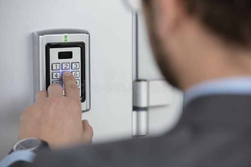 Ciérrese para arriba de código de sistema de seguridad de la mano del hombre de negocios que entra imagen de archivo libre de regalías