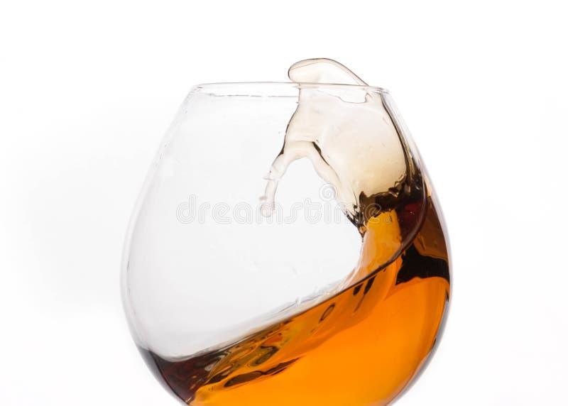 ciérrese para arriba de chapoteo del whisky marrón en vidrio transparente fotos de archivo libres de regalías