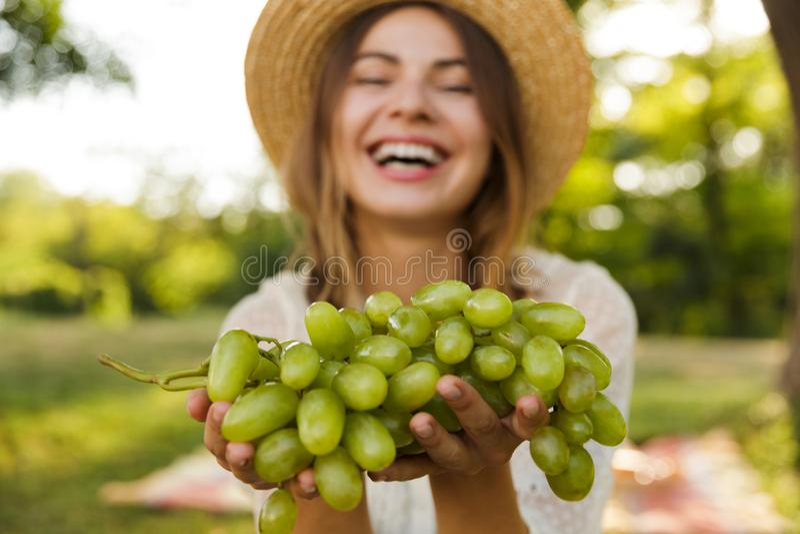 Ciérrese para arriba de chica joven de risa en tiempo del gasto del sombrero del verano en el parque imagen de archivo libre de regalías