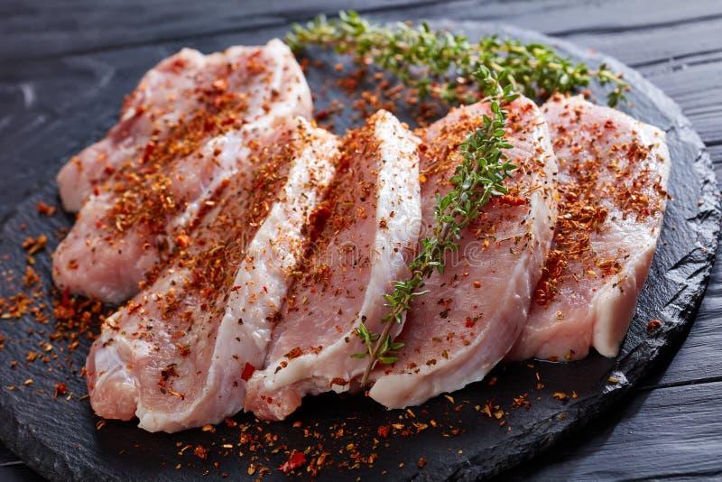 Ciérrese para arriba de chuletas de cerdo frescas con las especias y el tomillo imagen de archivo