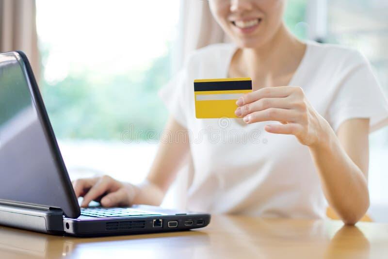 Ciérrese para arriba de compras femeninas en línea usando el ordenador portátil con el crédito Ca fotografía de archivo libre de regalías