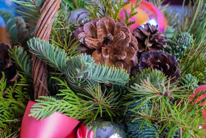 Ciérrese para arriba de conos del pino con las ramas del pino y de decoraciones coralinas y de plata en una cesta fotografía de archivo libre de regalías