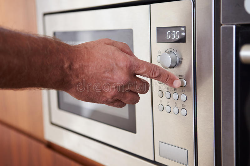 Ciérrese para arriba de contador de tiempo del ajuste de la mano en el horno de microondas imagen de archivo