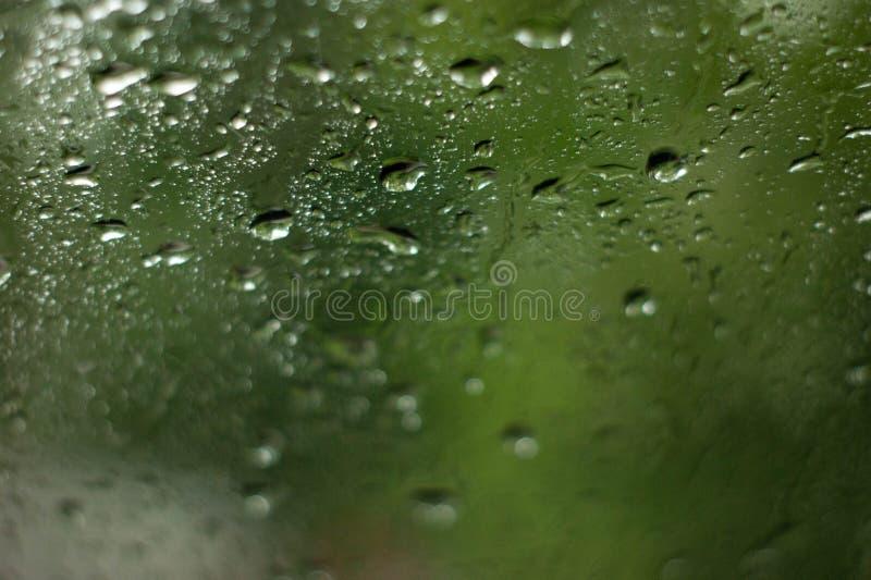 Ciérrese para arriba de descensos naturales del agua en la textura de cristal imagen de archivo