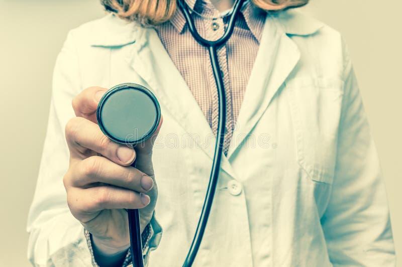 Ciérrese para arriba de doctor de sexo femenino con el estetoscopio en las manos imagenes de archivo