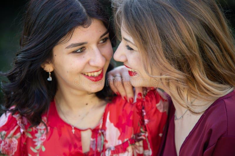 Ciérrese para arriba de dos amigos femeninos, uno rubio y la otra morenita está sonriendo alegre imagenes de archivo