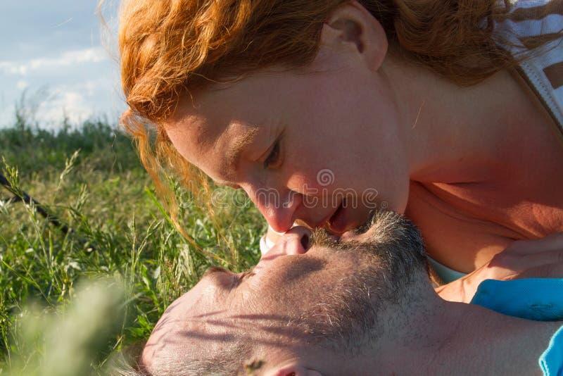 Ciérrese para arriba de dos caras antes de beso en hierba verde Ciérrese encima del beso del verano del hombre y de la mujer imagen de archivo