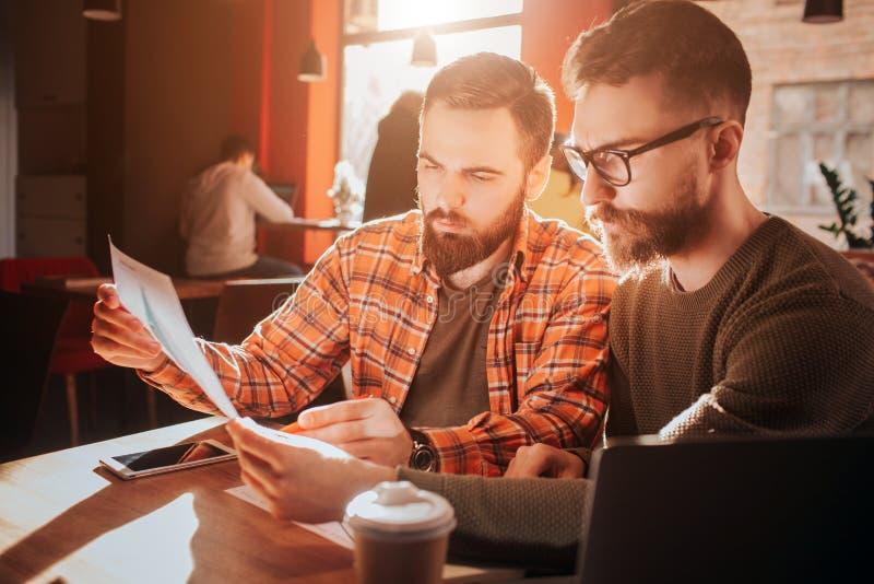 Ciérrese para arriba de dos inconformista-hombres de negocios que mirando a los papeles y a la información de aprendizaje de ello fotografía de archivo